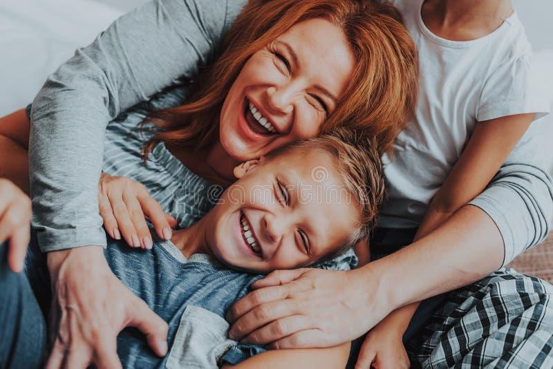 Lycklig moder och hennes son som tillsammans omfamnar royaltyfri bild