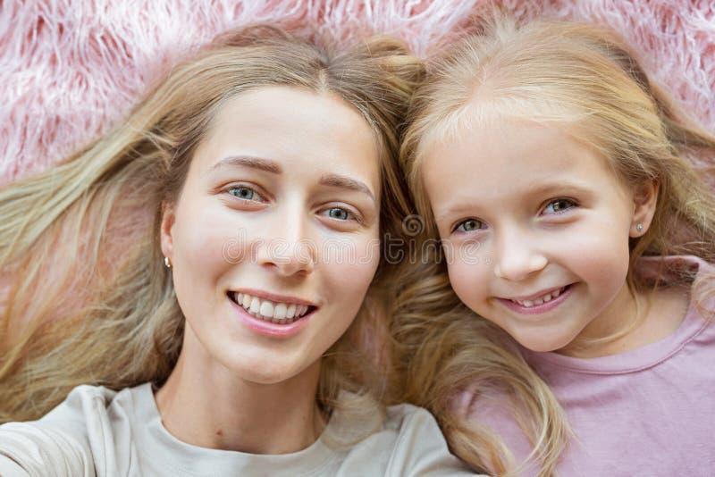 Lycklig moder och liten dotter med blont hår som ligger på rosa päls och gör selfie Två härliga personer, familjbegrepp royaltyfri fotografi