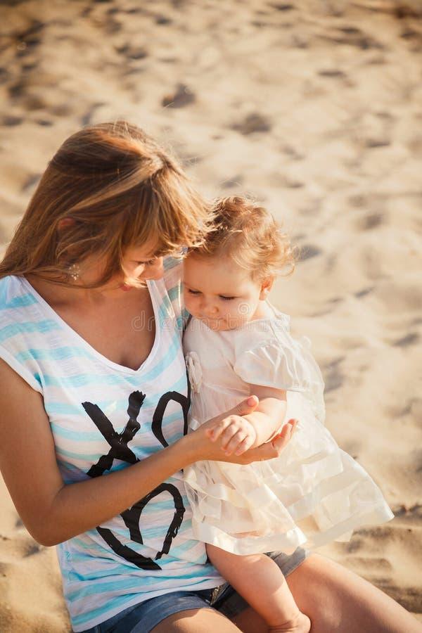 Lycklig moder och liten dotter som tillsammans sitter och spelar på stranden royaltyfria foton