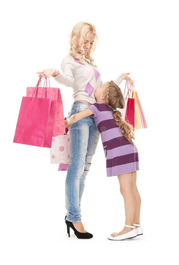 Lycklig moder och liten flicka med shoppingpåsar royaltyfri bild