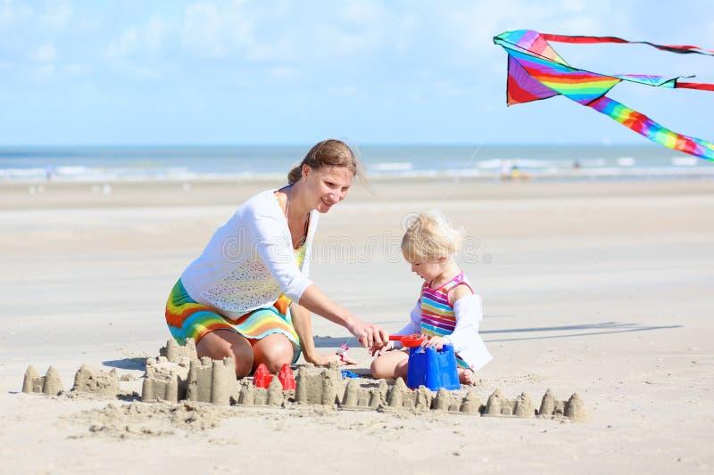Lycklig moder och litet barn som spelar på stranden royaltyfria bilder