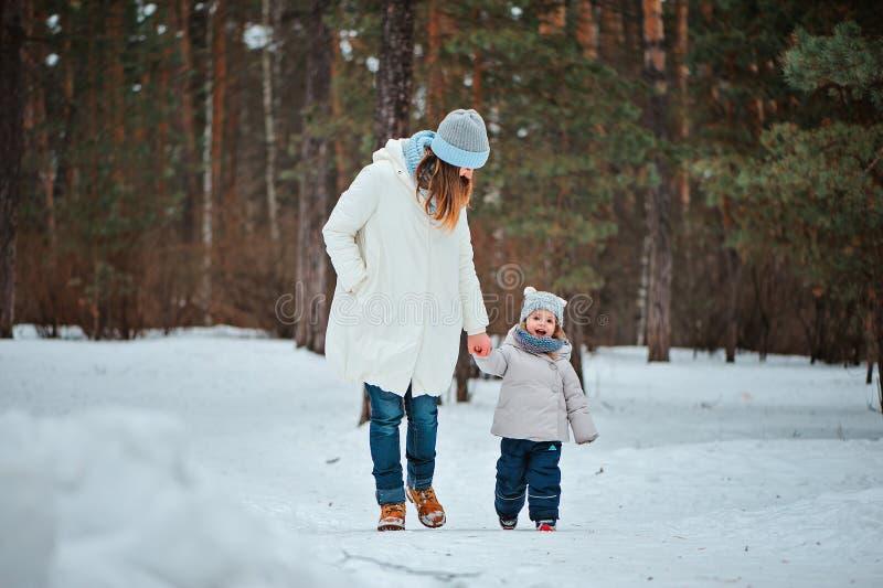Lycklig moder- och litet barndotter som går i snöig skog för vinter arkivbild