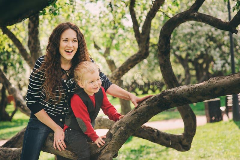 Lycklig moder- och litet barnson som tillsammans spelar utomhus- och klättrar äppleträdet arkivbild