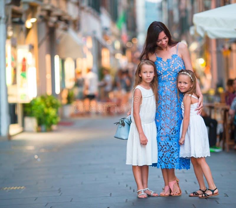 Lycklig moder och små förtjusande flickor på den hemtrevliga gatan under italiensk semester Europeisk semester för familj arkivbilder
