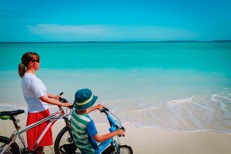 Lycklig moder och son som cyklar på stranden arkivfoto