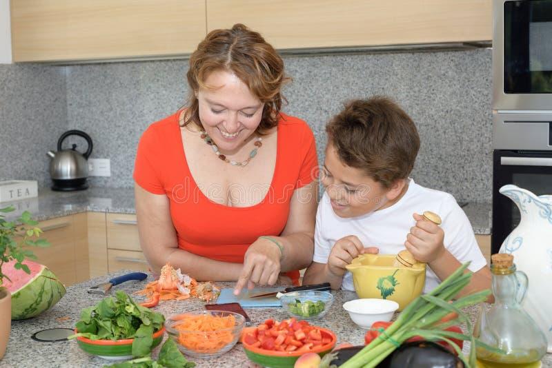 Lycklig moder och son som förbereder lunch med en mortel royaltyfri bild
