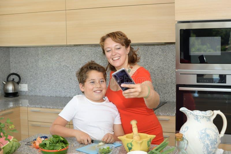 Lycklig moder och son som förbereder lunch, medan ta 'en selfie arkivbilder