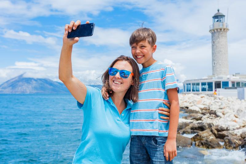 Lycklig moder och son som framme gör selfie av den Patras fyren, Peloponnese, Grekland royaltyfri foto