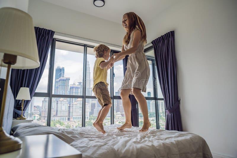 Lycklig moder och son som hoppar på sängen mot bakgrunden av ett stort fönster som förbiser skyskraporna och det stort royaltyfri bild
