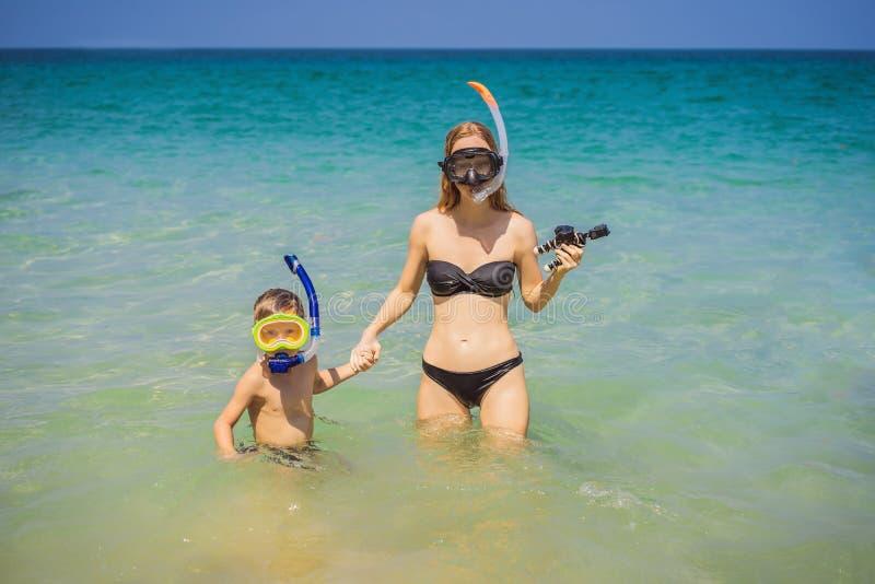Lycklig moder och son som snorklar p? stranden arkivfoton