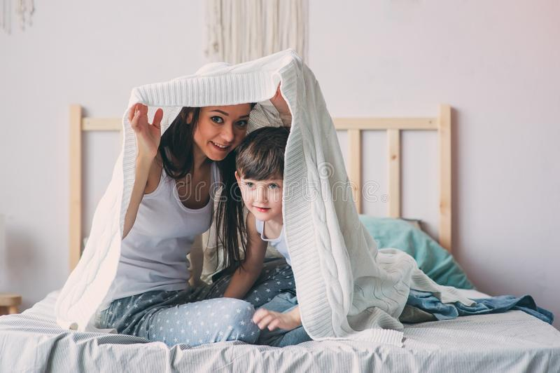 Lycklig moder och son som spelar och döljer under filten i säng royaltyfri foto