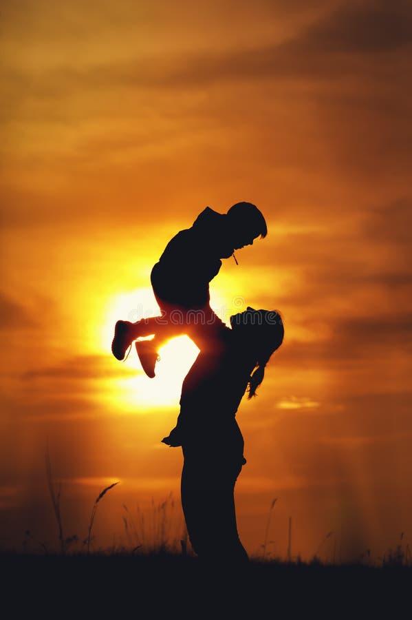 Lycklig moder och son som spelar mot inställningssolen royaltyfri fotografi