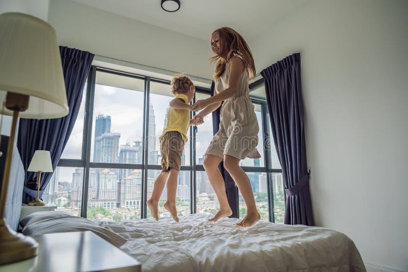 Lycklig moder- och sonbanhoppning på sängen mot bakgrunden av royaltyfria bilder
