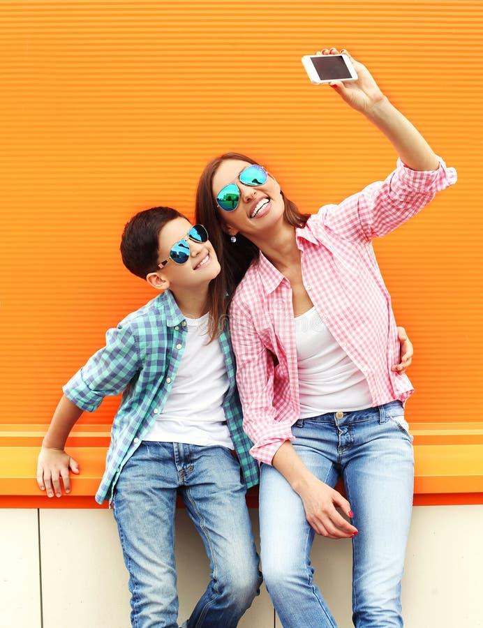 Lycklig moder- och sontonåring som tar bild självståenden på smartphonen i stad royaltyfri bild