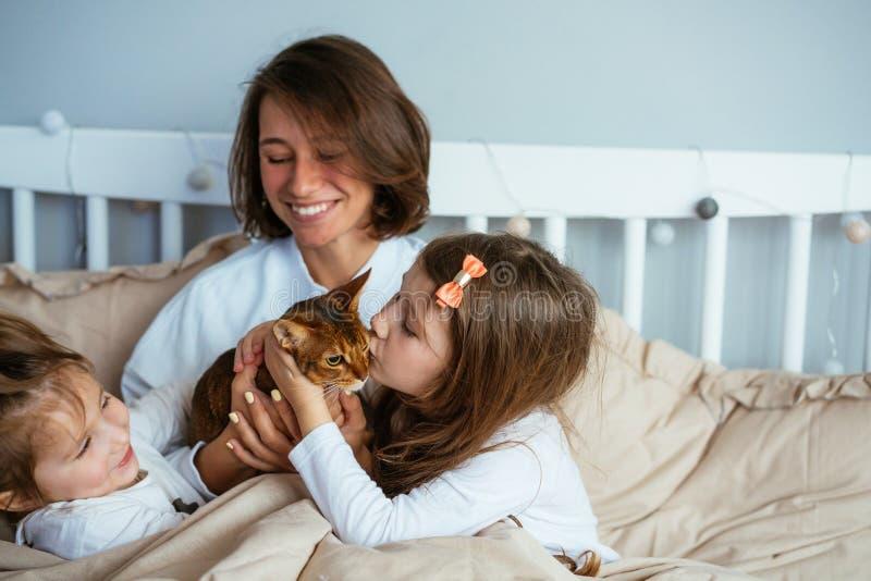 Lycklig moder och två döttrar som ler kramar i säng royaltyfri bild