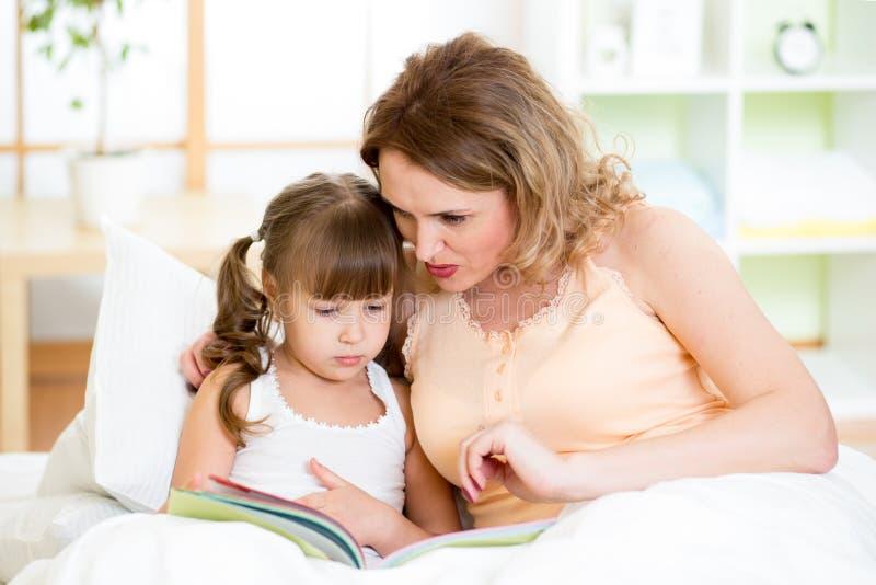Lycklig moder- och ungedotter som läser en bok arkivbild