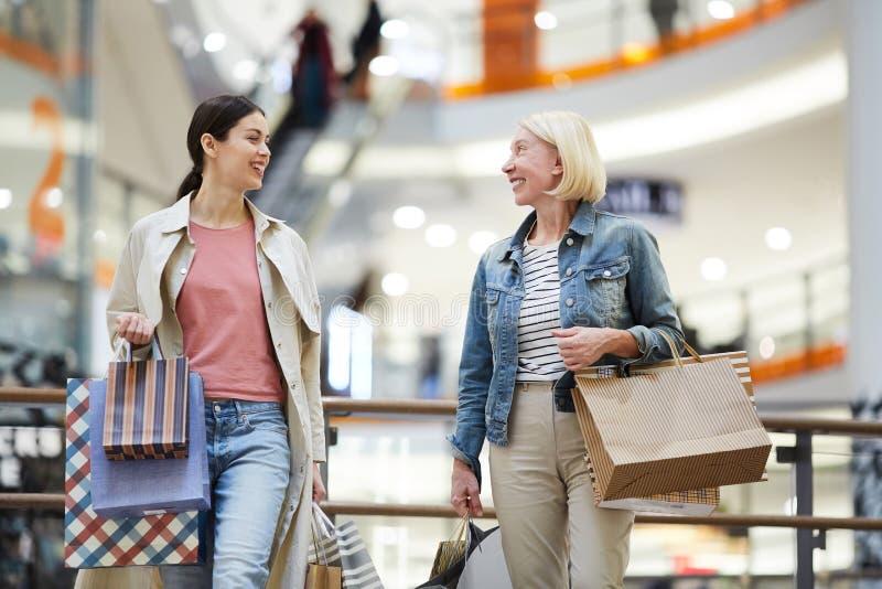 Lycklig moder och vuxen dotter som tillsammans gör shopping royaltyfria bilder