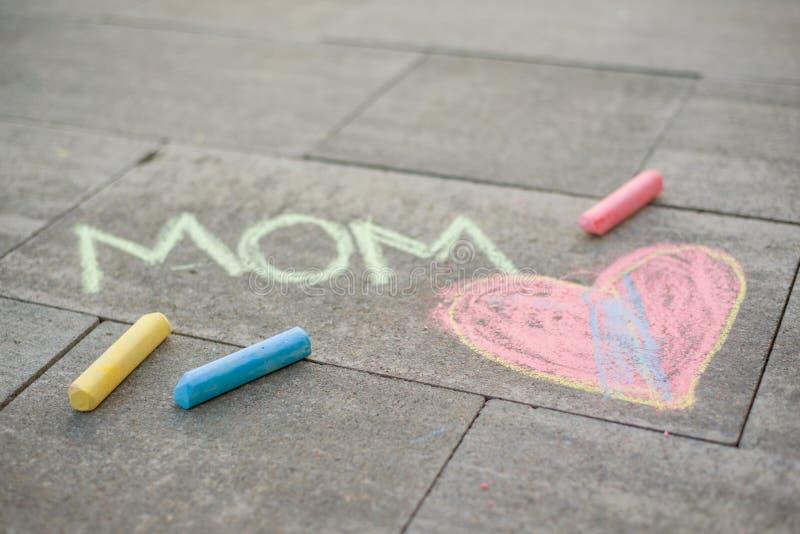 lycklig moder s för dag Barnattraktioner för hennes moder en bildöverraskning av färgpennor på asfalten Förälskelsemamma royaltyfri fotografi