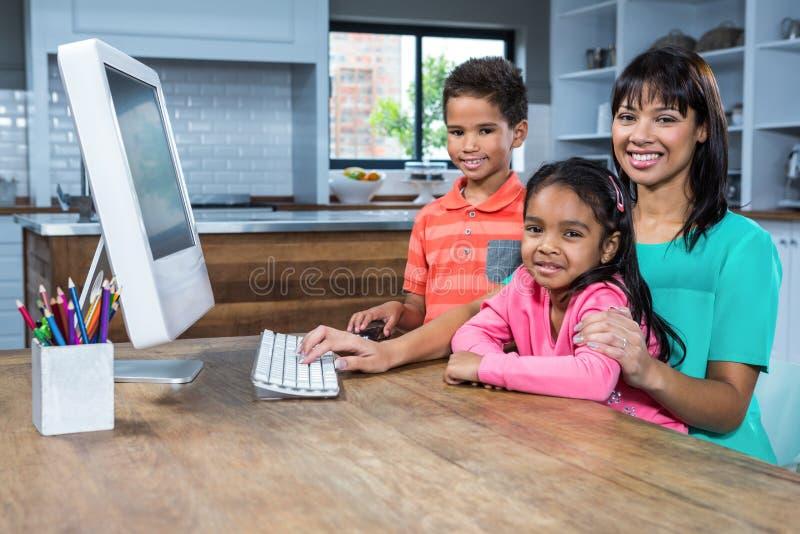 Lycklig moder som använder datoren med hennes barn arkivbilder
