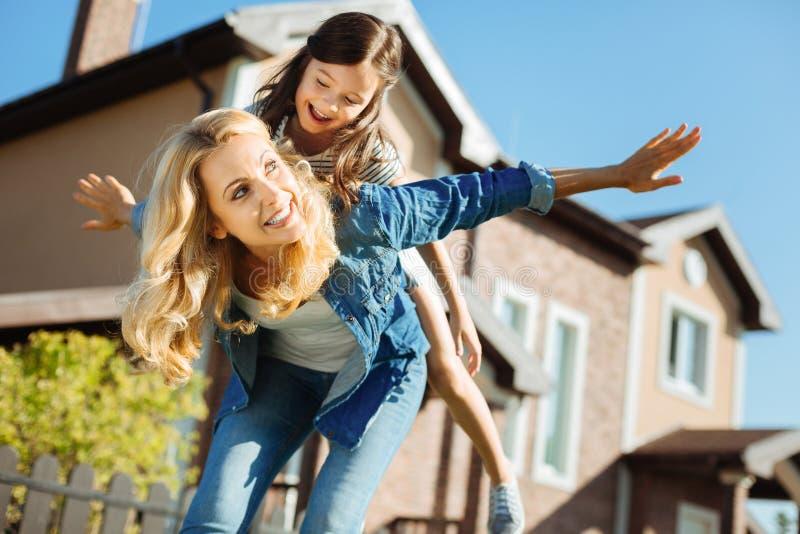Lycklig moder som bär hennes dotter på baksida fotografering för bildbyråer