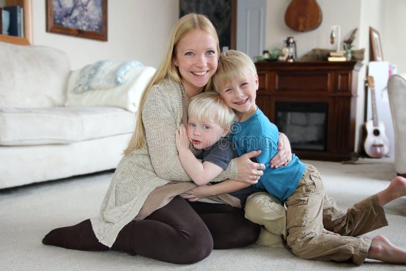 Lycklig moder som hemma kramar hennes två unga barn royaltyfri bild