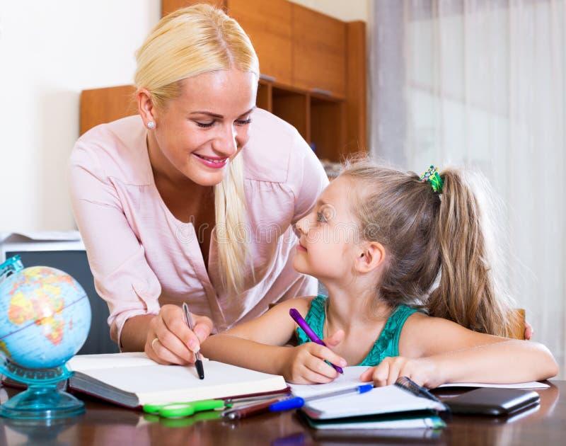 Lycklig moder som hjälper den lilla dottern arkivbild