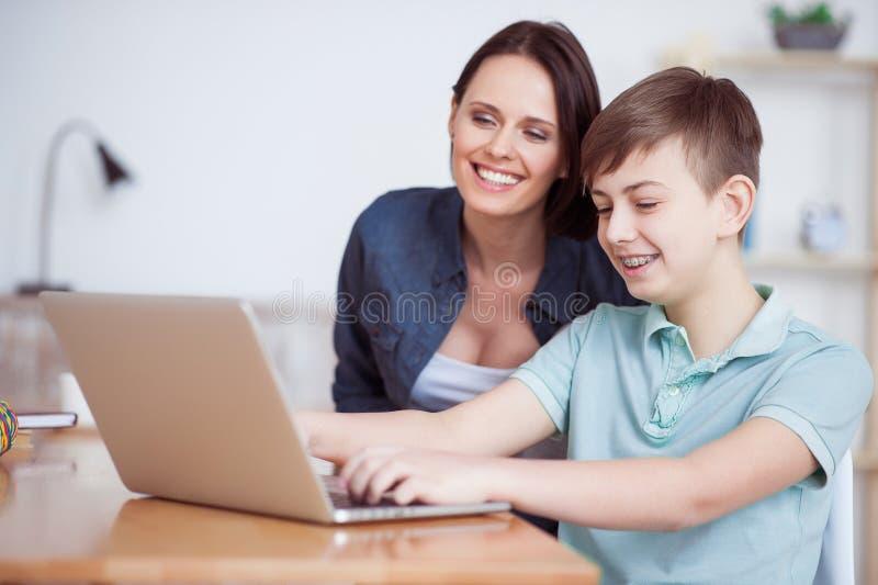 Lycklig moder som hjälper hans son att göra läxa royaltyfria bilder