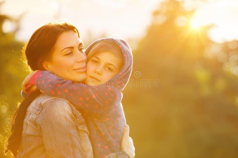 Lycklig moder som kramar dottern arkivbild