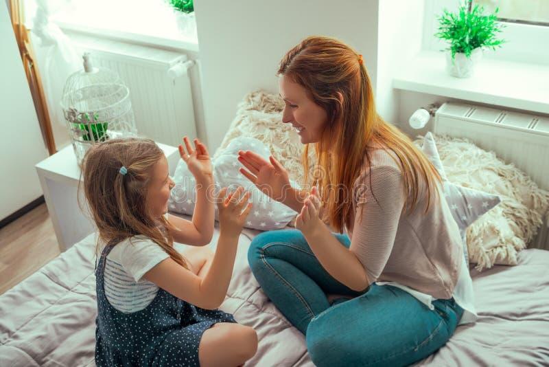 Lycklig moder som spelar med den hemmastadda dottern fotografering för bildbyråer