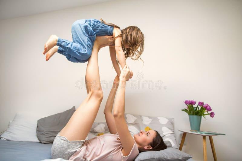 Lycklig moder som spelar med hennes hemmastadda dotter, dag för moder` s arkivfoto