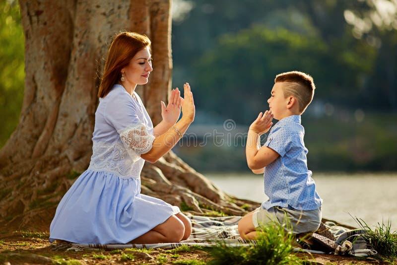 Lycklig moder som spelar med hennes son i parkera arkivbilder