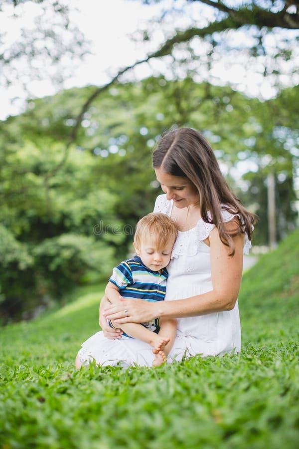 Lycklig moder som spelar med hennes son i parkera royaltyfria foton