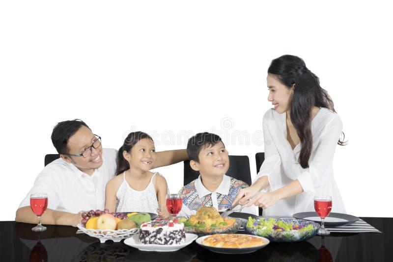 Lycklig moder som tjänar som hennes familj för att äta lunch tillsammans arkivfoton