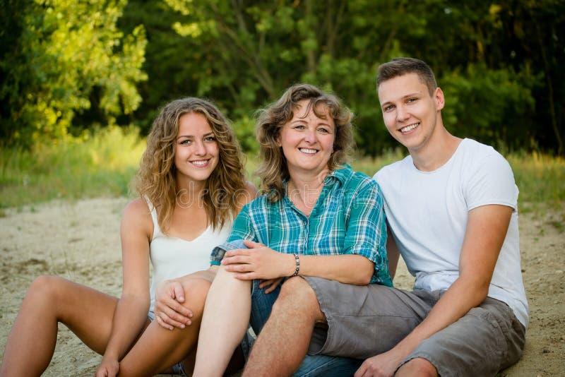Lycklig moder, son och dotter utomhus tillgiven familj arkivbilder
