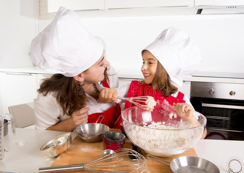 Lycklig moderbakning med den lilla dottern i förkläde- och kockhatt med mjöldeg på kök royaltyfri bild