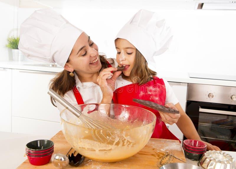 Lycklig moderbakning med den lilla dottern som äter chokladstången som används som ingrediensen, medan undervisa ungen royaltyfri foto