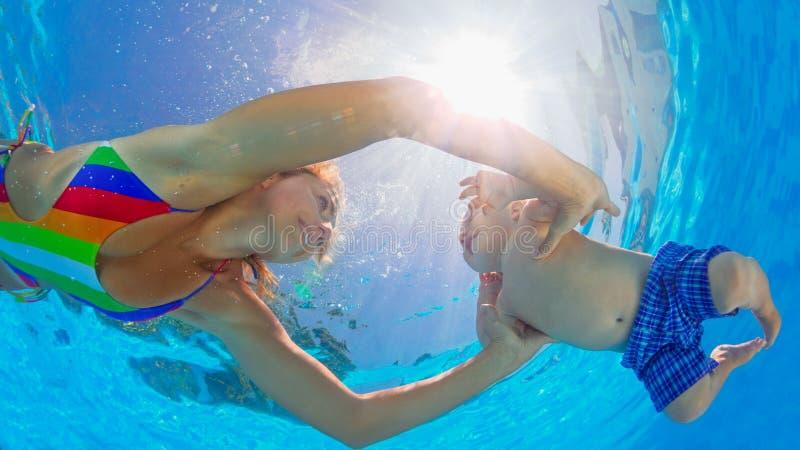 Lycklig moderdyk som är undervattens- med det lilla barnet i simbassäng royaltyfri fotografi