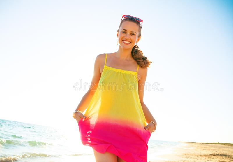 Lycklig moderiktig kvinna i färgrik klänning på kusten i afton royaltyfri fotografi