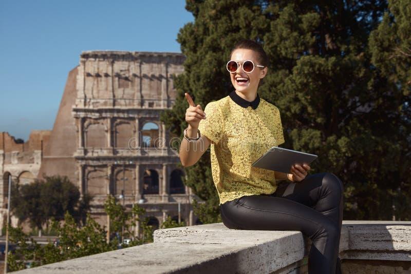 Lycklig moderiktig turist- kvinna med minnestavlaPC som pekar på något royaltyfri fotografi