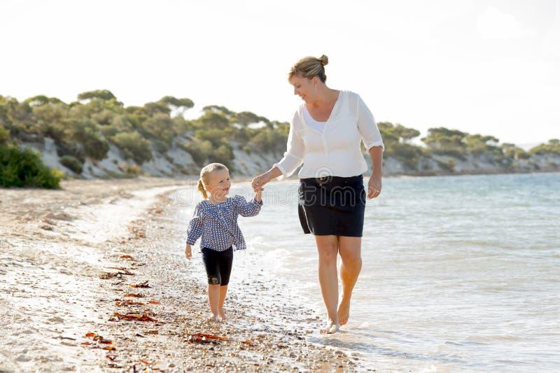 Lycklig moderinnehavhand av den söta blonda lilla dottern som tillsammans går på sand på strandhavskusten arkivfoto