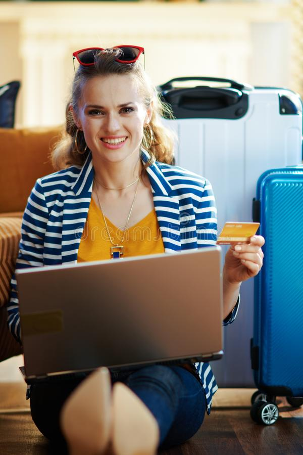 Lycklig modern kvinna med kreditkorten som bokar biljetter på bärbara datorn royaltyfria bilder