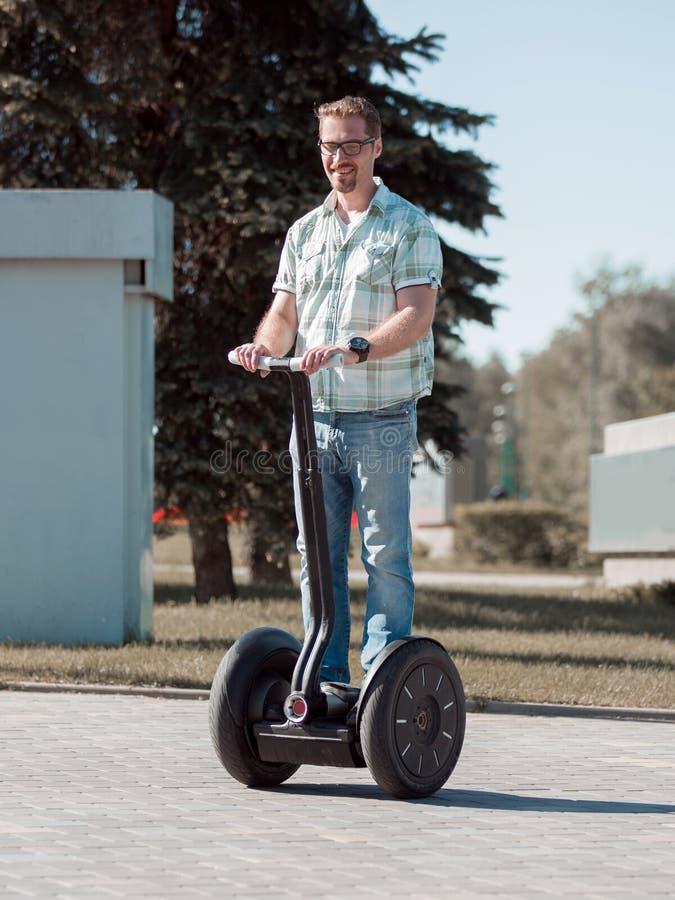 Lycklig modern man som rider en mini- hoverboard i parkera royaltyfria foton