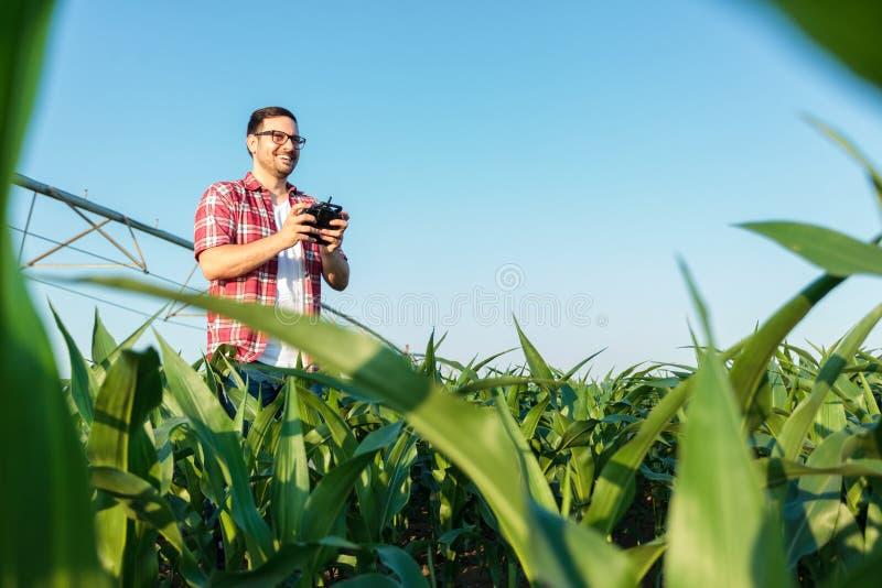 Lycklig modern ung bonde som kontrollerar hans fält med ett surr arkivbild