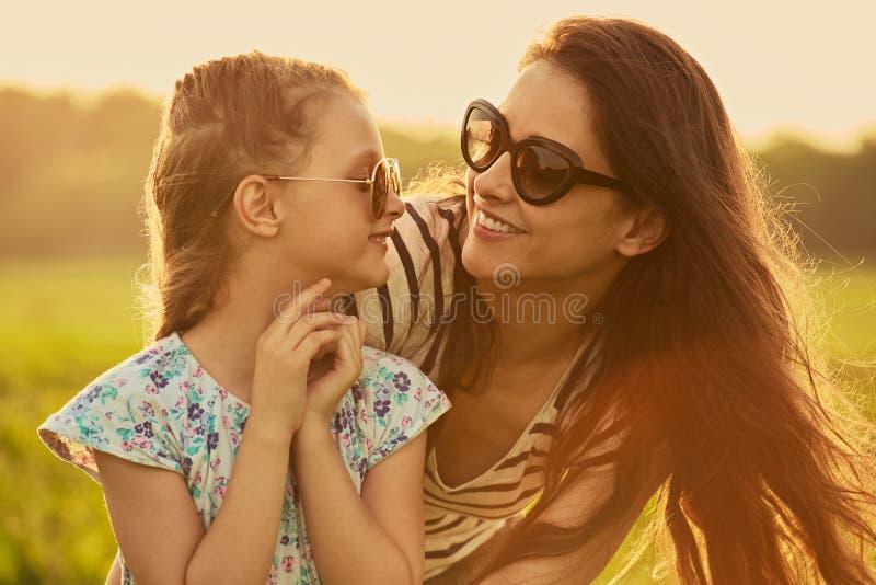 Lycklig modeungeflicka som omfamnar hennes moder i moderiktig solglasögon som ler och ser på de på naturbakgrund arkivbild