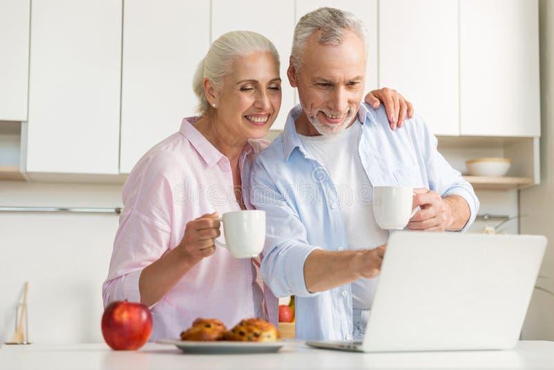 Lycklig mogen älska parfamilj som dricker te genom att använda bärbara datorn royaltyfria foton
