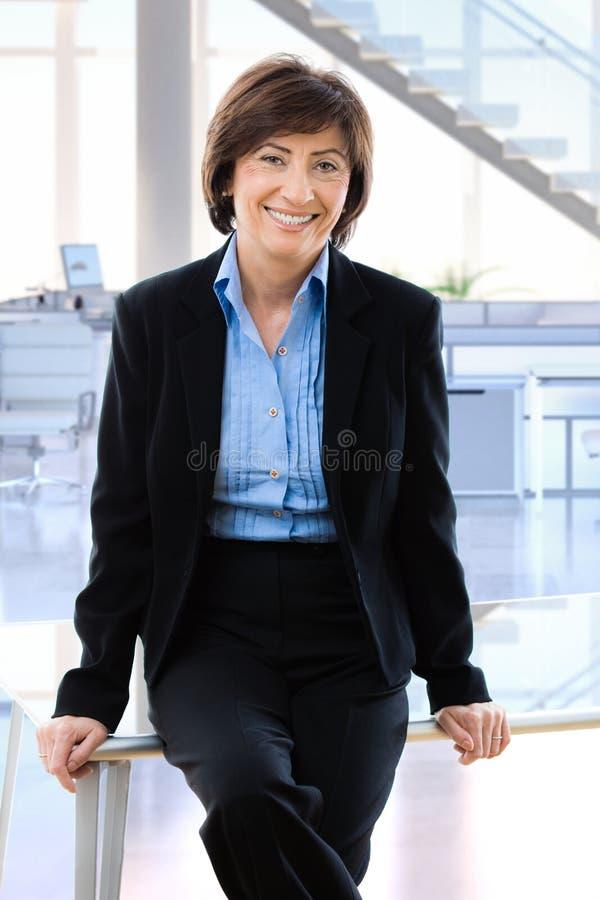 Lycklig mogen affärskvinna i regeringsställning arkivbild