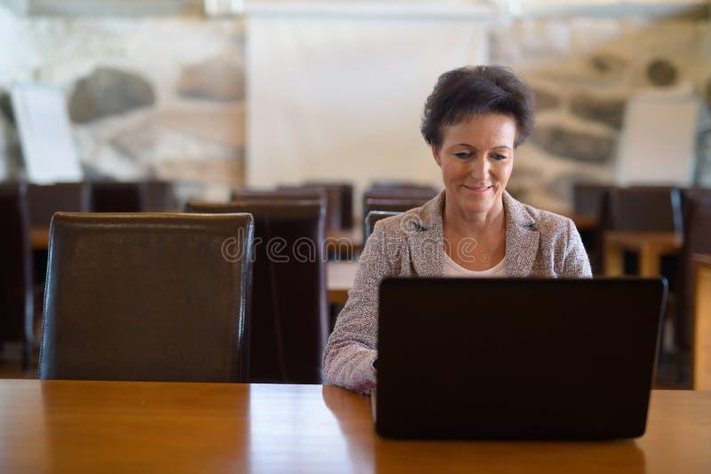 Lycklig mogen affärskvinna Using Laptop At coffee shop royaltyfria bilder