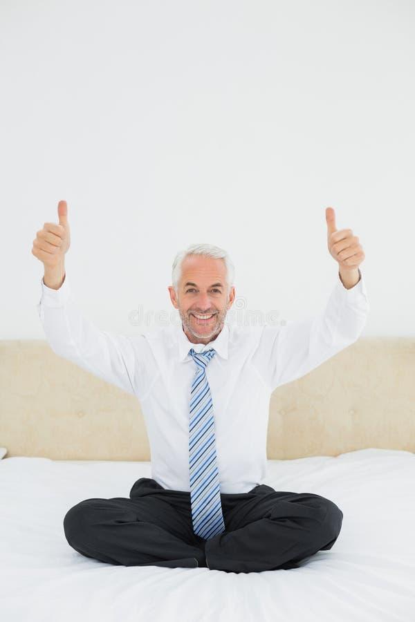 Lycklig mogen affärsman som gör en gest tummar upp på säng royaltyfri bild