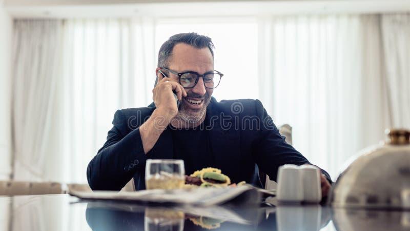 Lycklig mogen affärsman som talar på mobiltelefonen, medan sitta på den dinning tabellen i hotellrum Affärsman som har lunch och arkivbilder