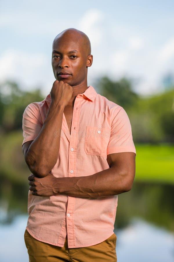 Lycklig mogen afrikansk amerikanman för stående som bär en rosa knappsommarskjorta och ser den utomhus- kameran Man med handen arkivbilder